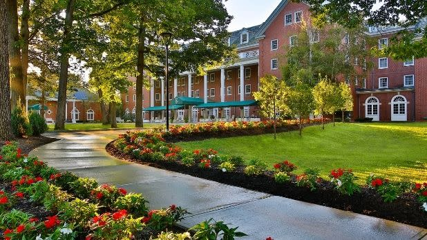 A shrubbery-lined walkway leads to the Gideon Putnam hotel