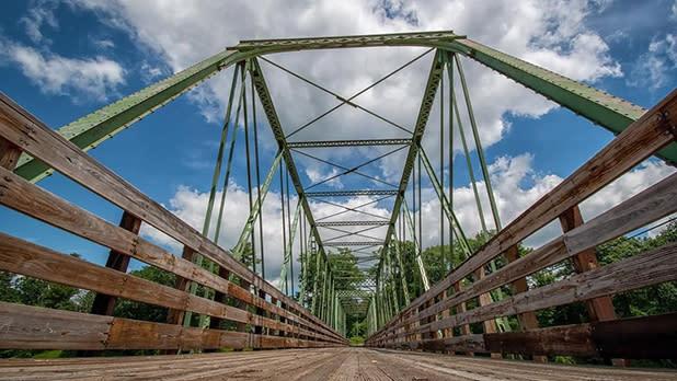 A wooden pedestrian bridge with a steel support overhead