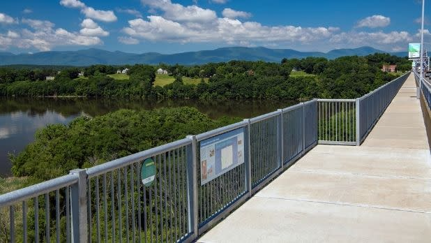 A pedestrian/bicycling path on a bridge with a view of the Catskill Mountains