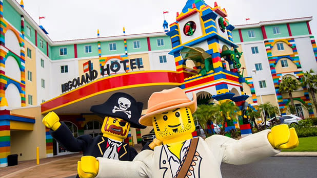 A pirate and another Lego figure in front of Legoland Hotel