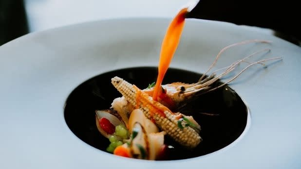 Sauce is poured over a prawn and Mexican corn dish at Las Puertas