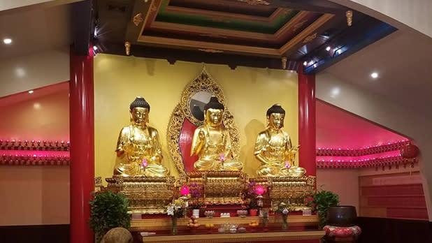 Three Buddhist statues on a shrine