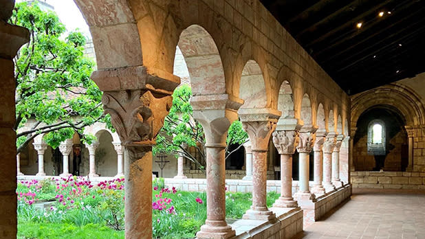 Flowers and greenery visible through Medieval arches