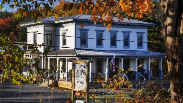The Mill Pond Inn with sign in foreground and fall foliage