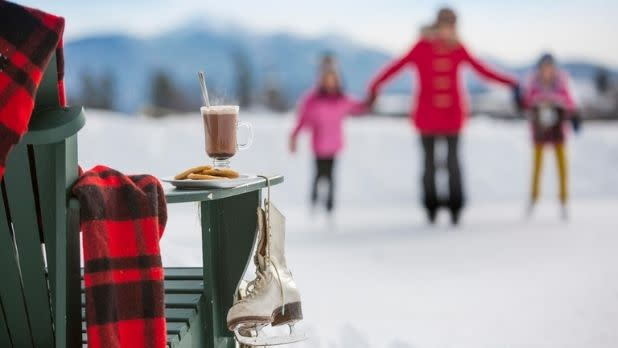 A woman and two children hold hands while ice skating, plus hot chocolate, skates, and a red and black blanket in foreground