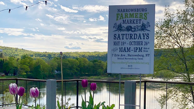 Narrowsburg Farmers Market sign with water and mountains behind it