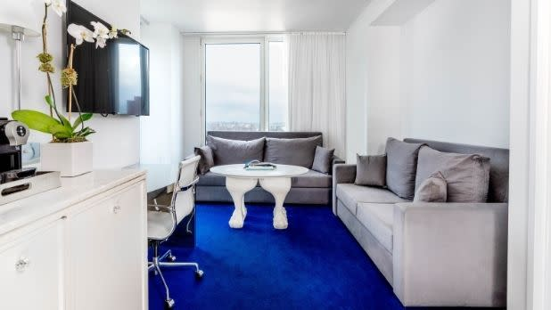 A hotel room with white furniture and blue carpeting at Nomo Soho