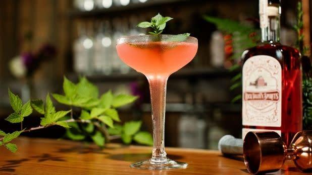 A raspberry vodka gimlet on a bar