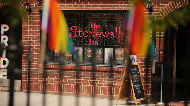 The Stonewall Inn with neon sign and Pride flags in foreground