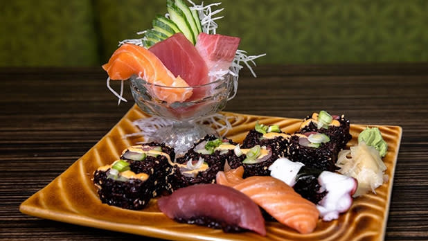 Black rice sushi and pieces of sashimi on a plate