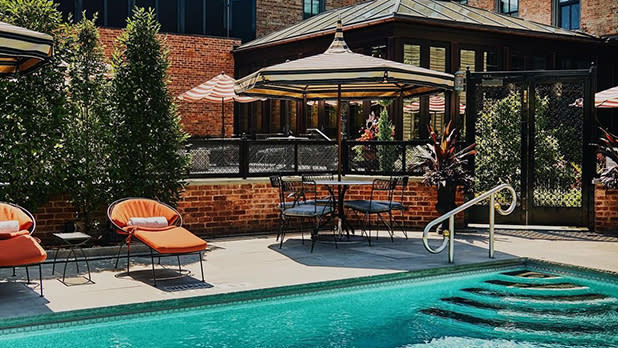 A pool, lounge chairs, and part of a building