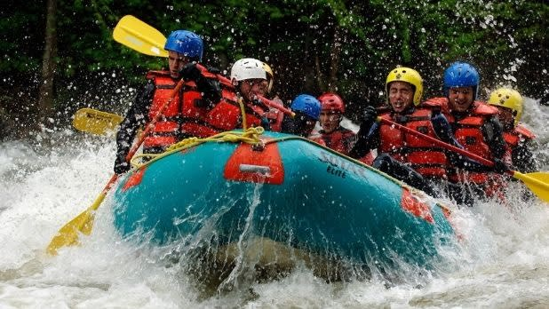 A group of people whitewater raft in the Adirondacks