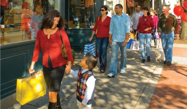 Groups of people walking along downtown Frederick shops with bags
