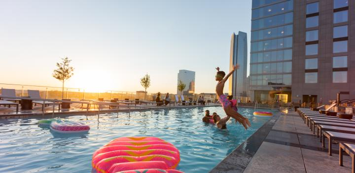 Boy jumping into the rooftop pool at the OMNI Hotel