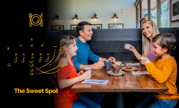 Family of four eating and drinking at coffee shop