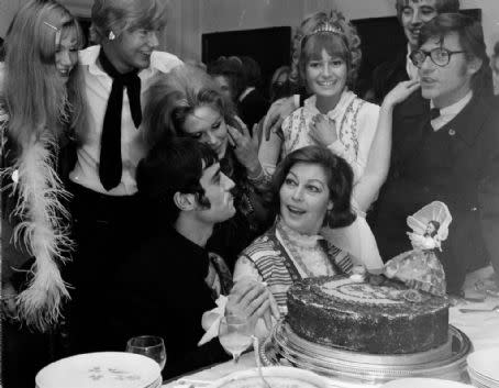 Ava Gardner sits in front of a large birthday cake surrounded by cast of The Ballad of Tam Lin including Ian McShane and Roddy McDowall.