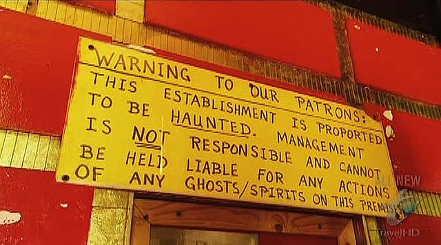 A yellow sign that reads, Warning to Our Patrons. This Establishment is purported to be HAUNTED. Management is NOT responsible and connato be held liable for any actions of any ghosts/spirits on this premesis