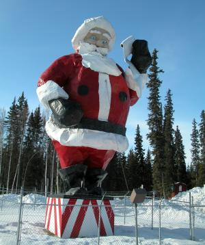 Large outdoor statue of Santa Claus in a traditional red suit with spruce trees and blue sky in background