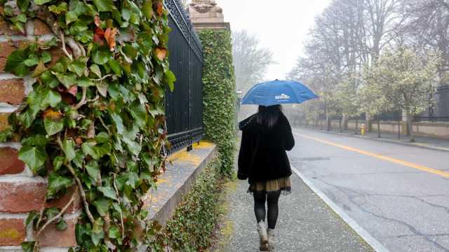 Woman walking down the street with an umbrella in Newport RI