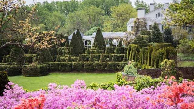The Main House at Ladew Topiary Gardens with beautiful flowers and topiaries in front of the house
