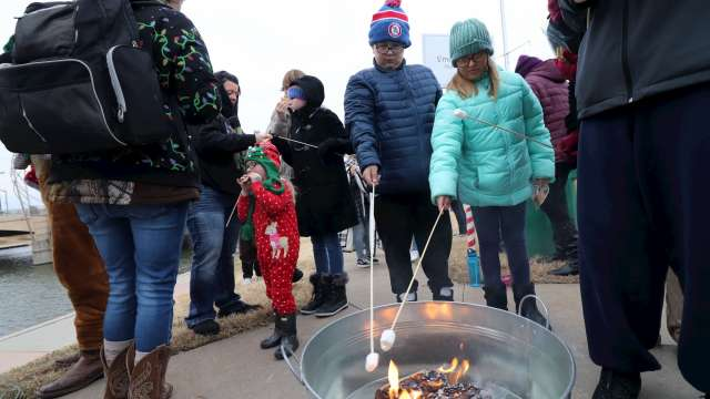 Families roast marshmallows over a bonfire in Old Town