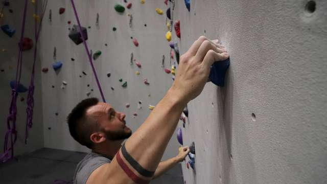 A man looks for his next handle while climbing the wall at Bliss Climbing and Fitness