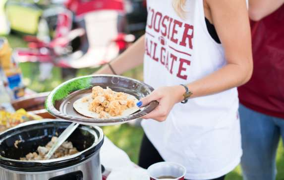 Woman's hands holding a plate of food wearing a Hoosier Tailgate shirt