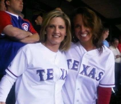 Women pose in Texas Rangers jerseys at a game