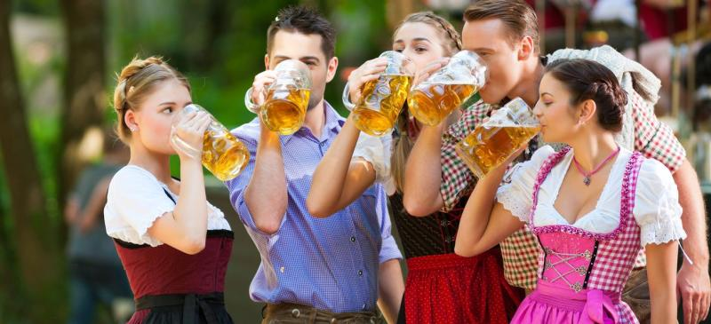 Group of five 20-somethings - three women dressed in German garb and two men in modern clothes - drink beer from large glass steins at OMNI Brewing Co's Oktoberfest