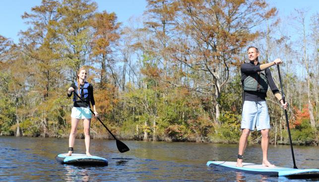 Two people with life jackets stand up paddle boarding in Chesapeake