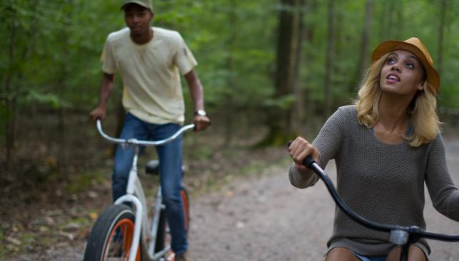 A man and a woman riding bikes outdoors in Chesapeake, VA