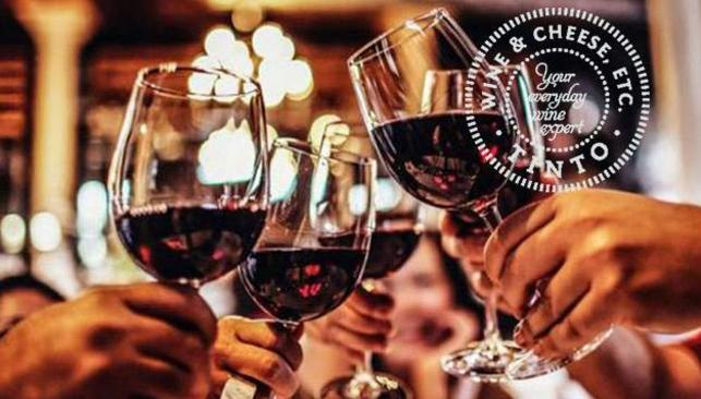 People clinking glasses of red wine to cheers, at Tinto Wine and Cheese