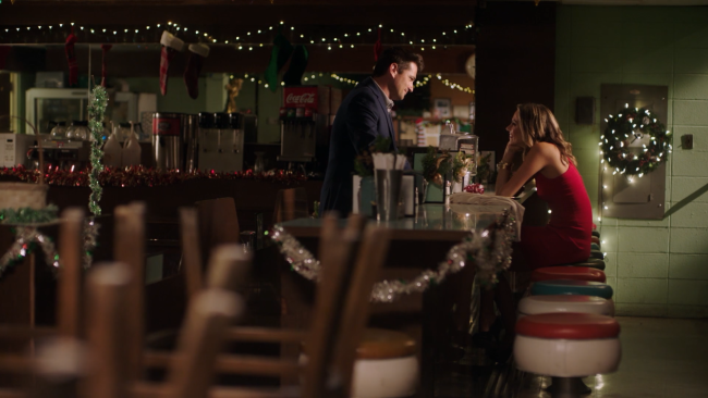 A man and a woman at a counter in a diner.