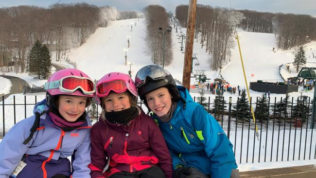 Happy kids on a family ski trip at Seven Springs