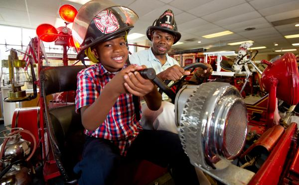 A kid and his dad wearing fire hats on an old fire truck at the Vintage Fire Museum
