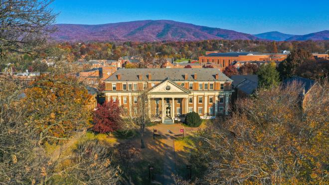 Aerial shot of the Roanoke College Administration building framed by fall color on trees in the foreground and fall color mountains in the background.