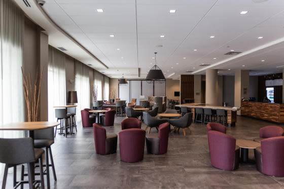 The main lobby filled with a mix of high-top tables and coffee tables with maroon colored chairs at the Courtyard by Marriott Elkhart