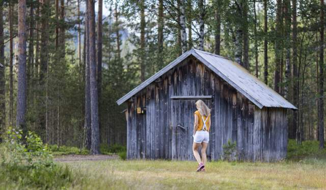 Woman walking past cabin in Gjerstad