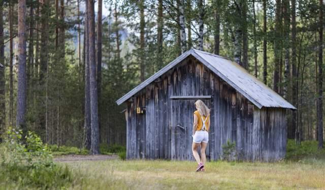 Woman walking past cabin in Gjerstad