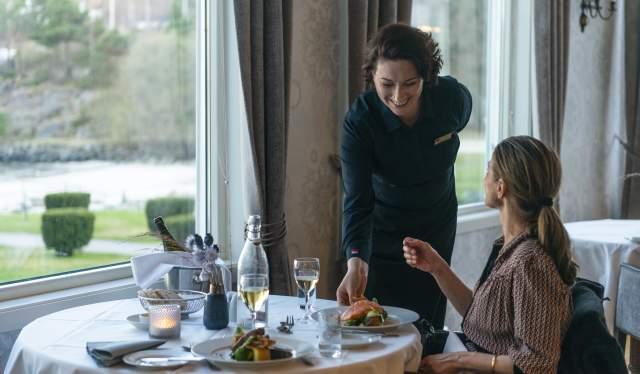 Hovmester Nadia Dumitriu serverer middag på Strand Hotel Fevik