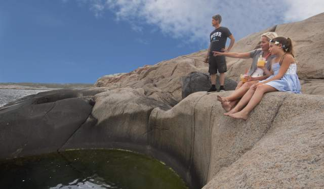 Family sitting on the edge of giant pothole