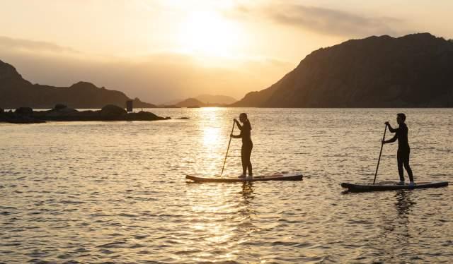 SUP-padlere i solnedgang ved Korshamn Rorbuer i Lyngdal