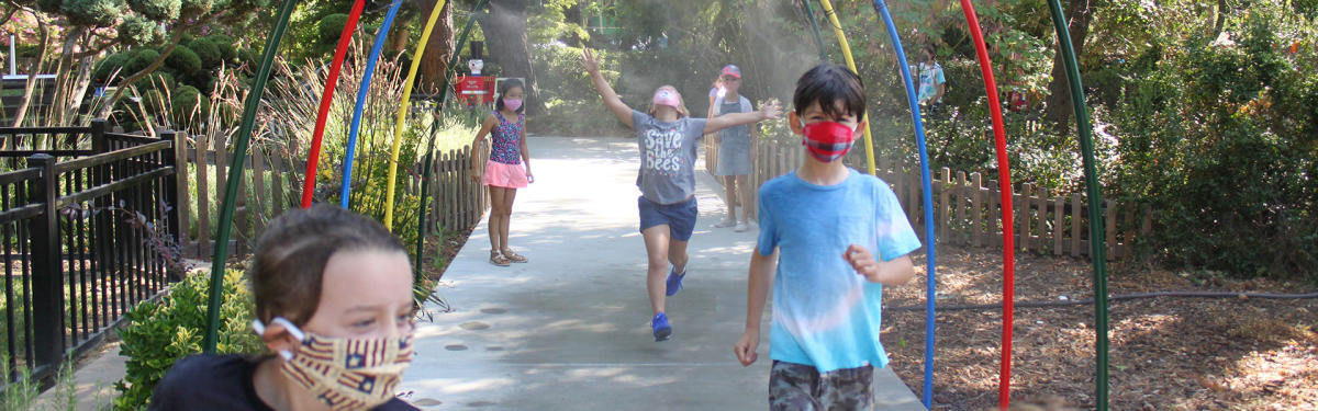 children enjoying misters at outdoor park