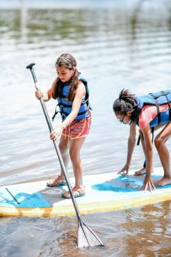 two young girls launch a paddle board from the Rowing Dock in Austin Texas