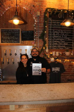 Fall Street Brewing Owners Brad and Anna Luisi-Ellis pose in front of the bar with their November 2020 business of the month plaque