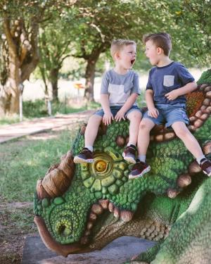 Two boys, roaring while sitting on top of a dinosaur at The Heard