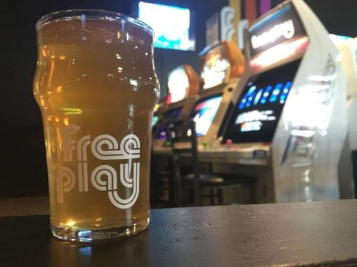 Photo of beer in front of arcade games at Free Play Arlington