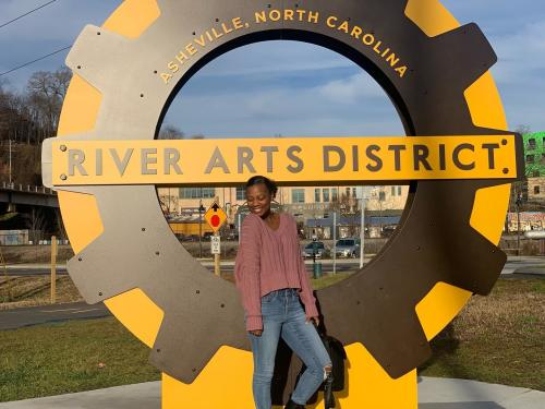 A woman poses with new signage in the River Arts District in Asheville, NC