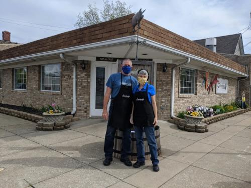 Couple in masks standing in front of Geraldine's Kitchen