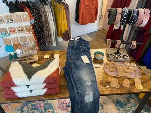 A display table with clothing and jewelry in the Hazel Jane Boutique.